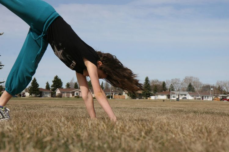 Side view of girl doing cartwheel on field against sky