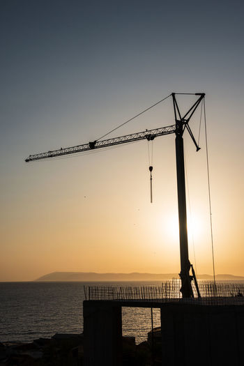 Silhouette crane at construction site against sky during sunset