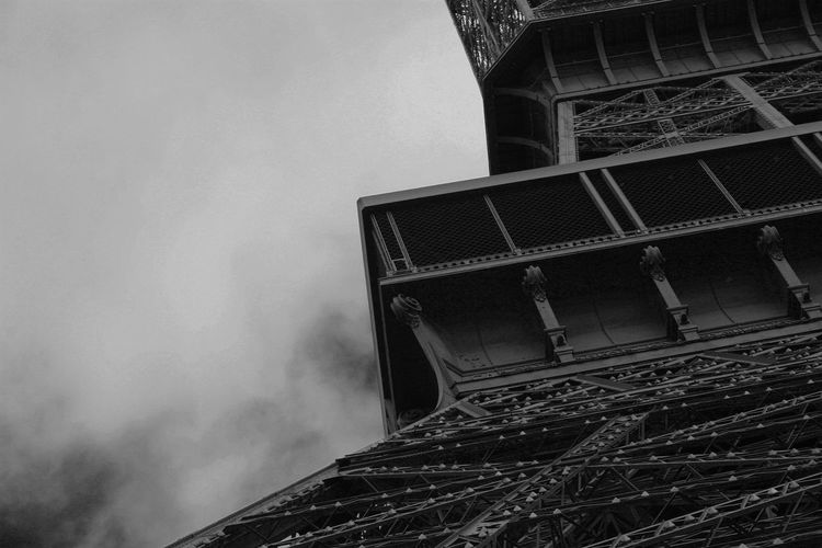 Cropped image of eiffel tower against cloudy sky