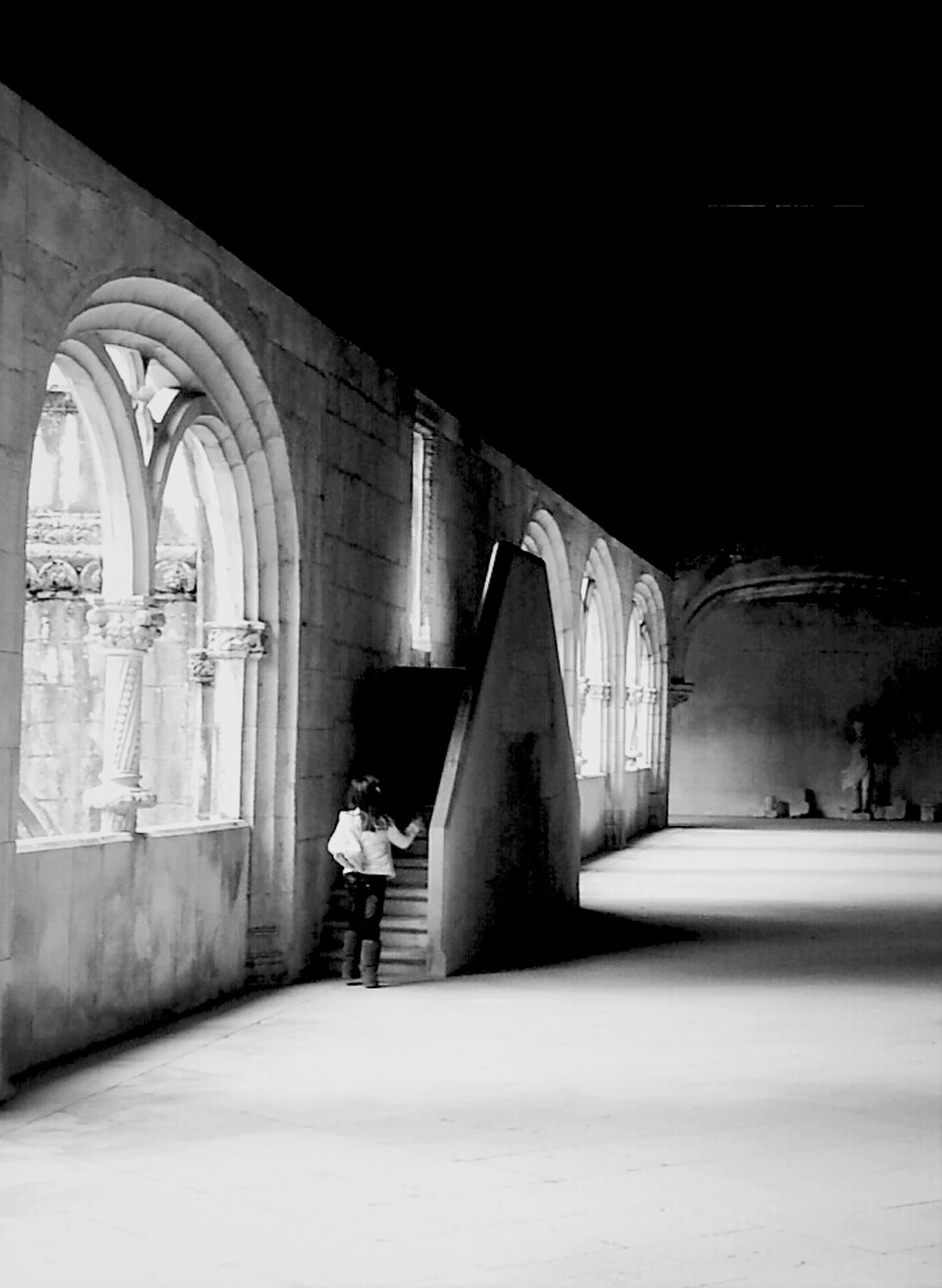 architecture, built structure, arch, rear view, men, lifestyles, the way forward, indoors, full length, walking, copy space, night, tunnel, person, leisure activity, building exterior, illuminated