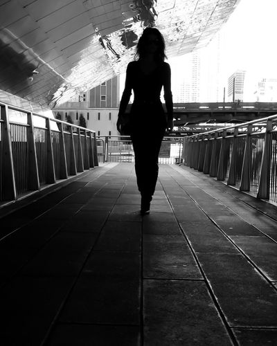 Rear view of woman standing on railing
