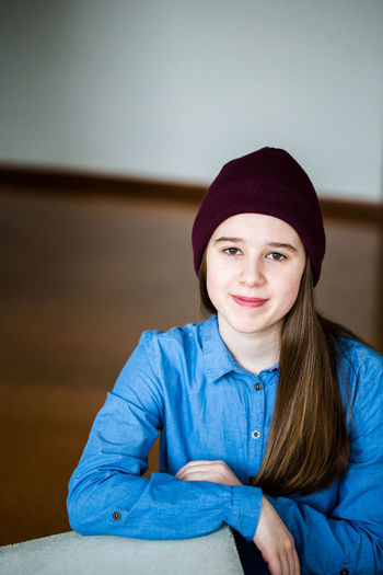 Portrait of smiling young girl sitting at home