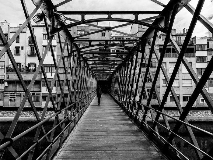Footbridge over footpath amidst buildings