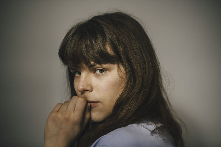 Portrait of young woman looking away against white background