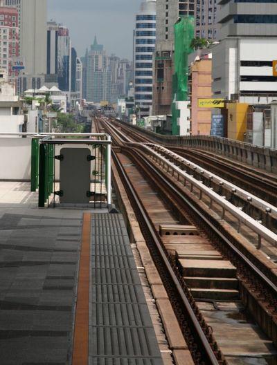 Railroad station platform against buildings in city