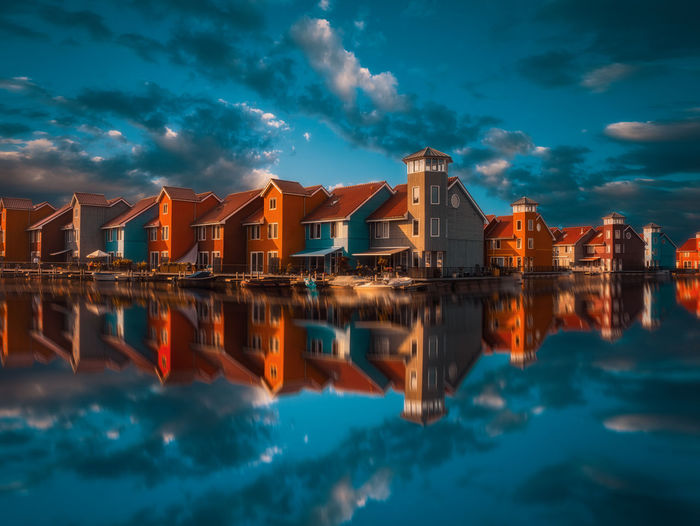 Reflection of illuminated buildings in sea against sky at dusk
