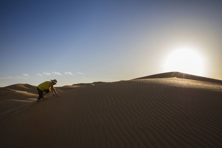 Senior woman climbing on sand dune at desert