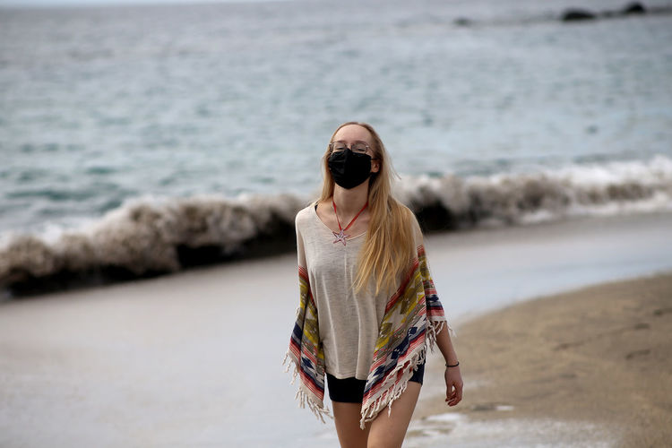 Portrait of woman wearing mask walking at beach