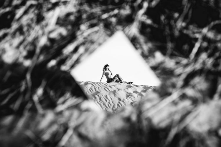 Reflection Of Woman Sitting On Sand In Mirror