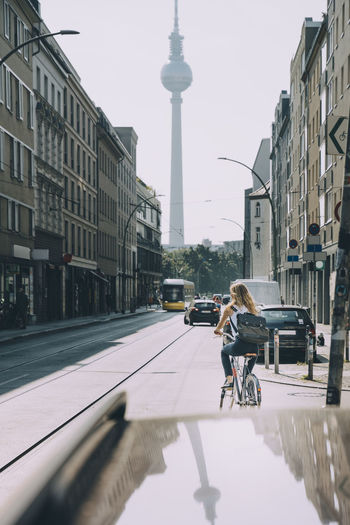 Man riding bicycle on city street amidst buildings
