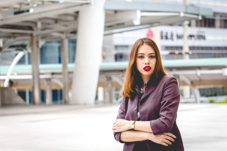 Portrait of beautiful young businesswoman standing on walkway in city