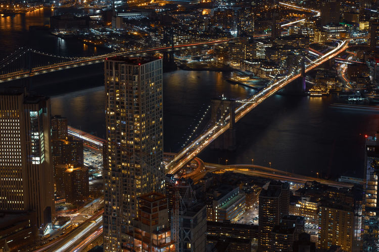 High angle view of illuminated brooklyn bridge over river in city at night