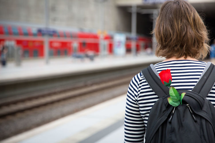 Backpack Brown Hair Day Focus On Foreground Hairstyle Journey Mode Of Transportation One Person Outdoors Positive Emotion Public Transportation Rail Transportation Railroad Station Railroad Track Real People Rear View Red Red Rose Standing Station Track Transportation Travel Waiting Women