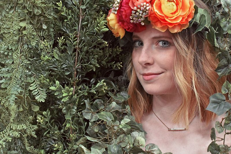 Portrait of beautiful young woman in red flowering plants