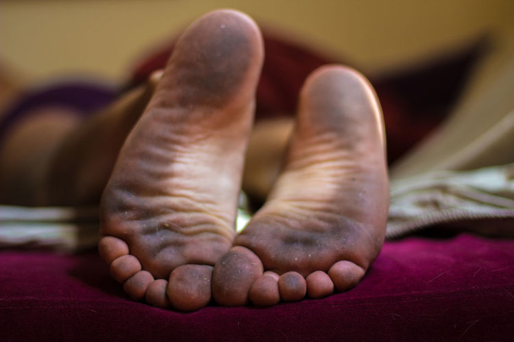 Close-up of messy feet of person lying in bed at home