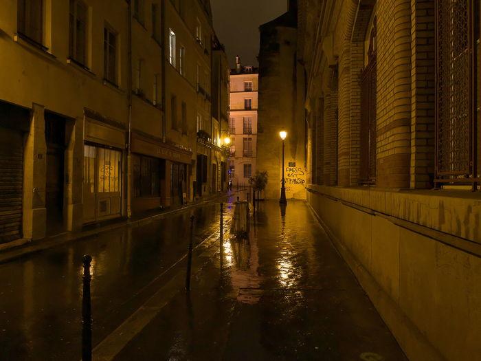Illuminated street by city against sky at night