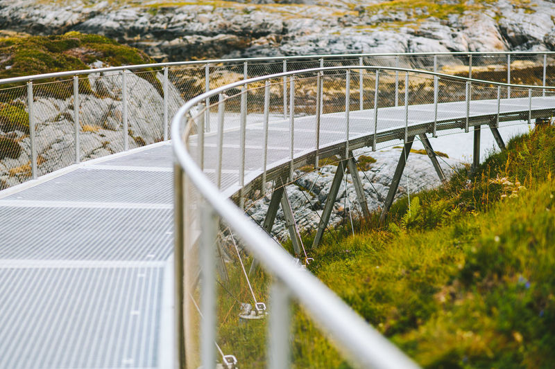 Footbridge by grass and rock formation