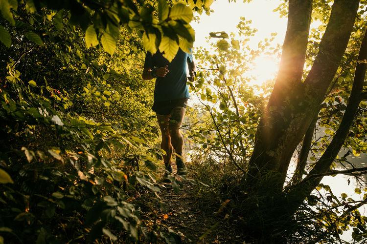 Full length of man running amidst plants