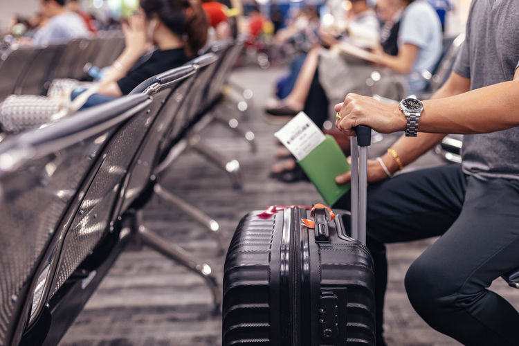 Midsection of man with luggage sitting at airport