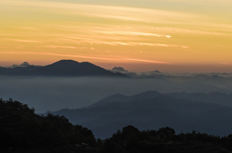 Scenic View Of Silhouette Mountains Against Orange Sky During Sunrise