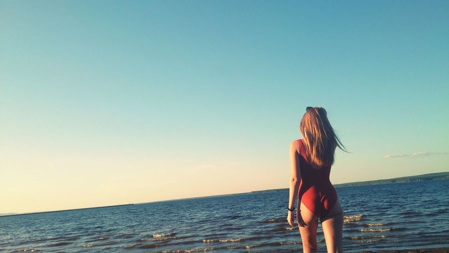 Rear view of sensuous woman in swimsuit walking on shore against blue sky