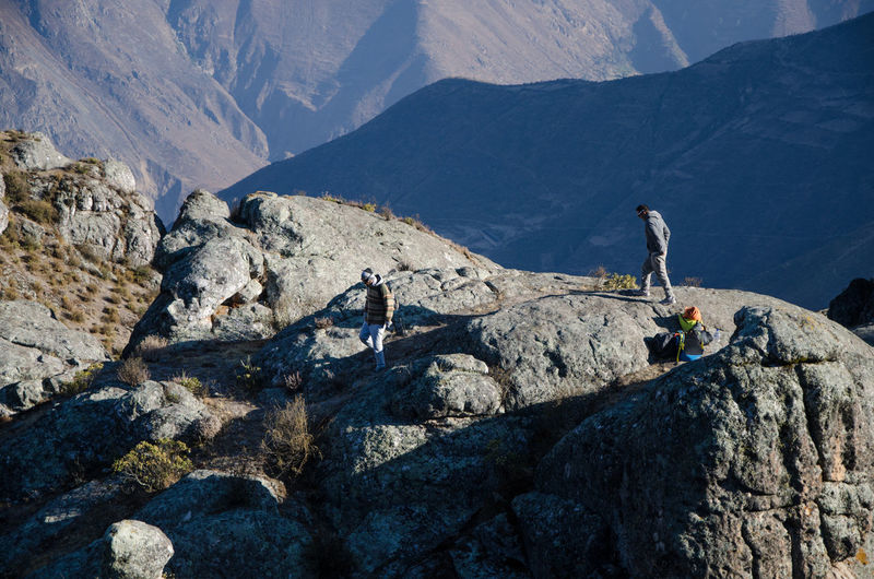 People on rocks against mountains