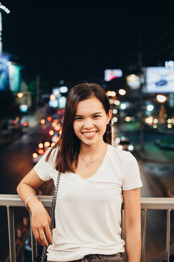 Portrait of smiling woman standing in city at night