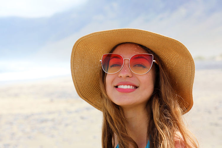 Portrait Of Smiling Young Woman Wearing Sunglasses And Hat At Beach