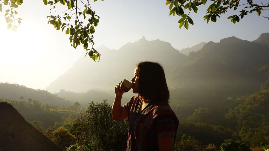 Woman drinking coffee by mountains against sky