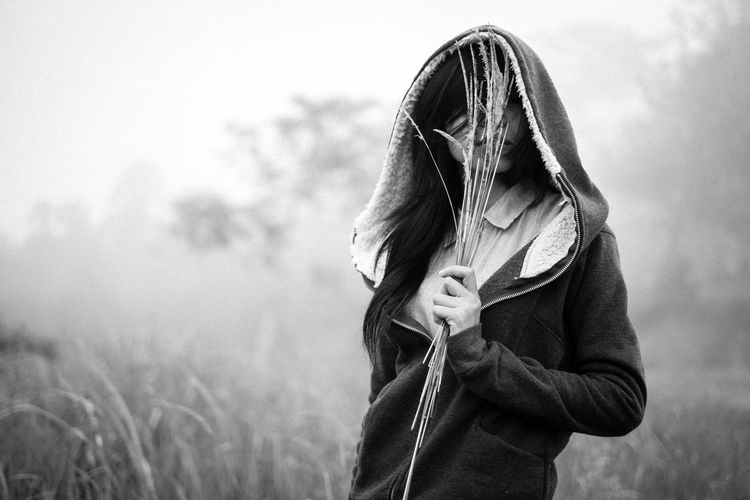 Woman wearing mask standing on field during winter
