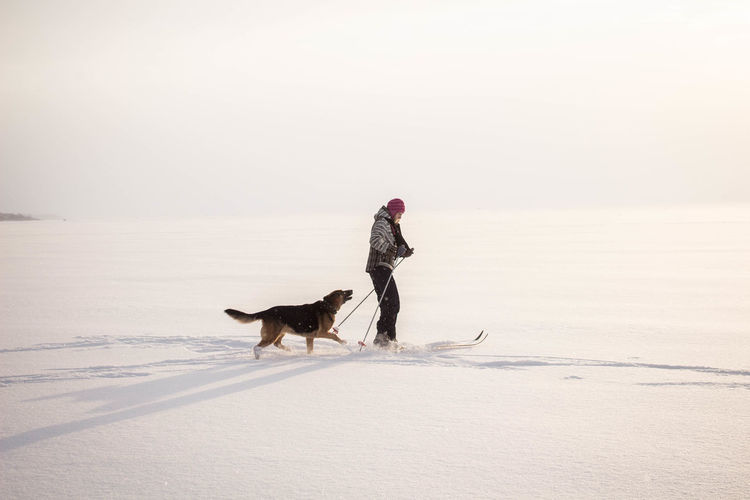View of woman walking with dog on snow covered beach