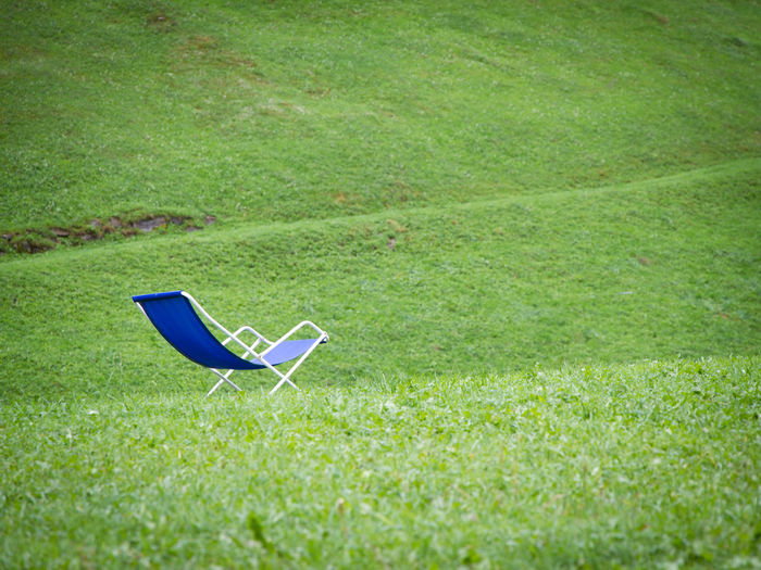 High angle view of empty chair on field