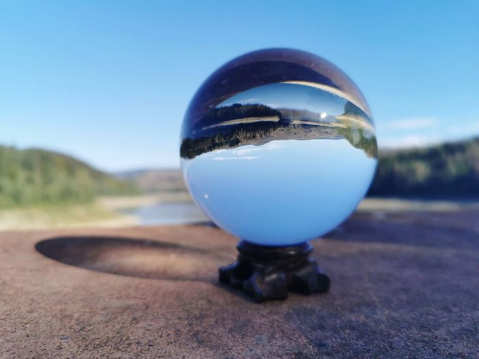 Close-up of crystal ball on glass against blue sky