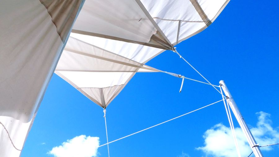 Low angle view of white fabric roof against blue sky