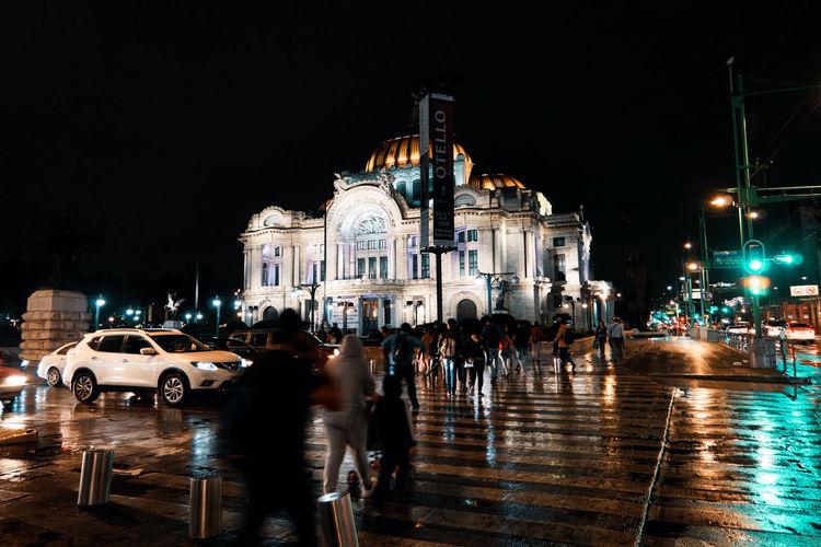 People on street against buildings at night