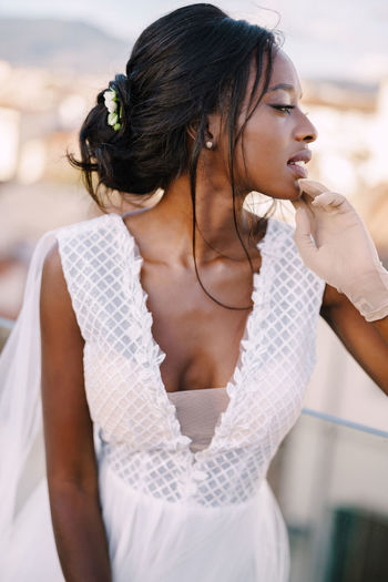 Portrait of bride looking away while standing outdoors