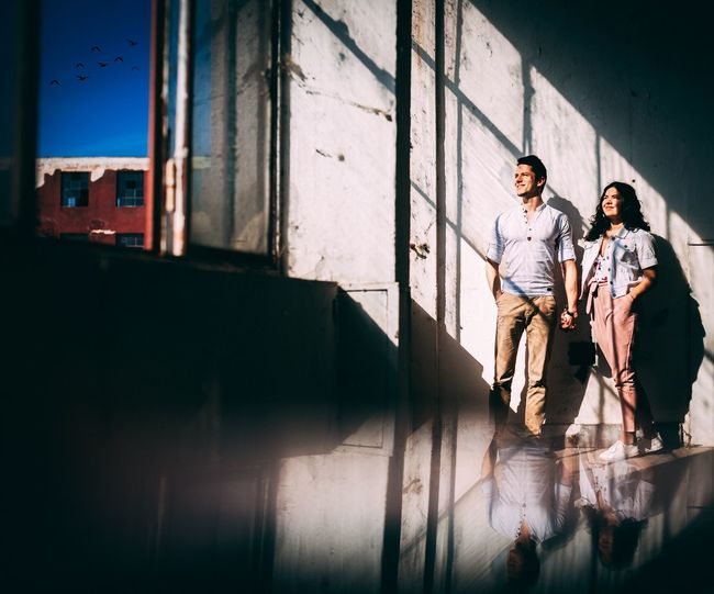 Creative photoshoot with couple standing against wall