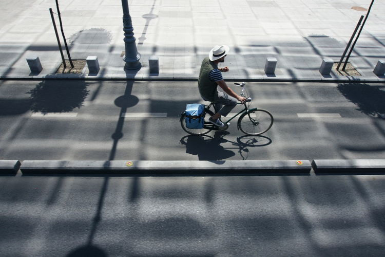 High Angle View Of Man Riding Bicycle On Road During Sunny Day