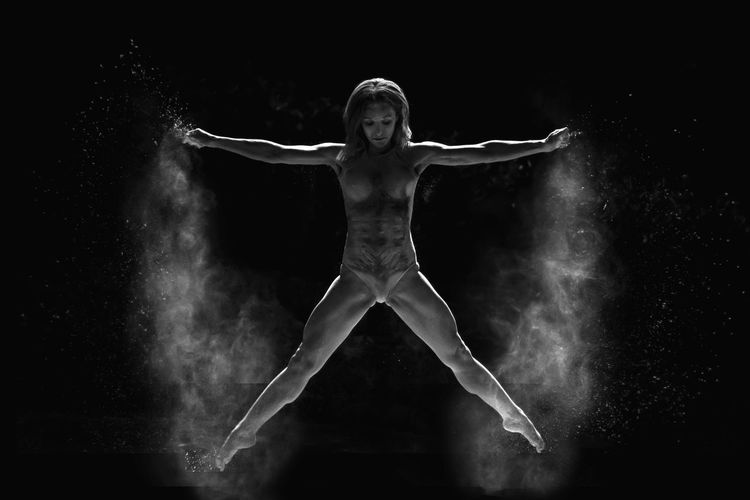 Full length of muscular woman jumping against black background