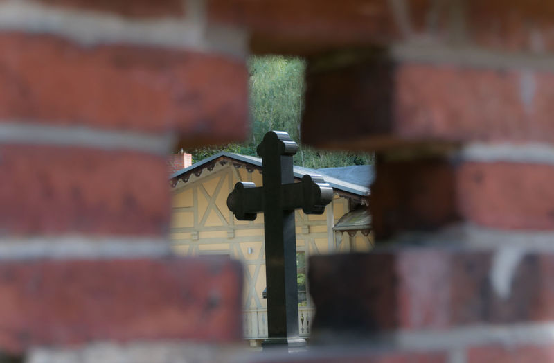 Cross seen through hole on brick wall