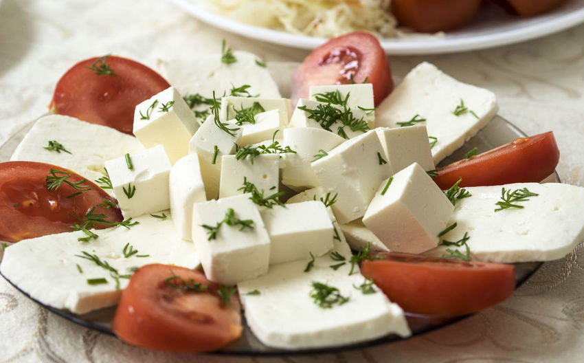 Close-up of feta cheese with tomatoes served in plate on table