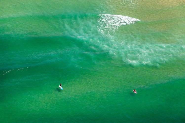 High Angle View Of Friends Paddleboarding In Sea