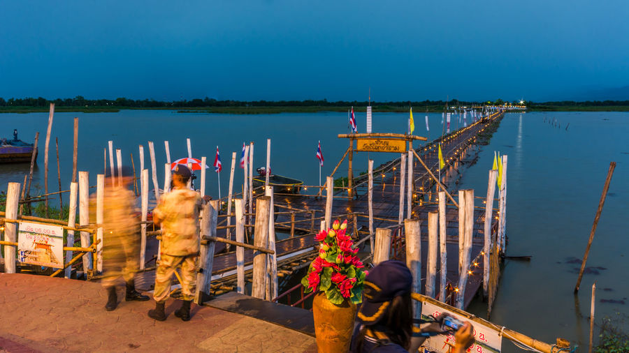 Soldiers standing by bamboo bridge and phayao lake against sky at dusk