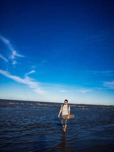 Man standing on beach against blue sky
