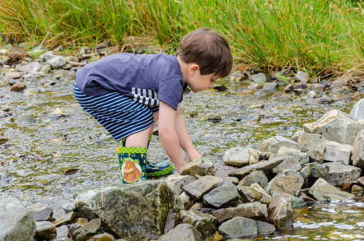 A young boy playing in a stream. Children Fun Adventure Bending Over Boy Casual Clothing Child Childhood Day Full Length Nature One Boy Only One Person Outdoors Outdoors Photograpghy  Outside Pebble People Playing Rock - Object Rocks Standing Stones Stream Water