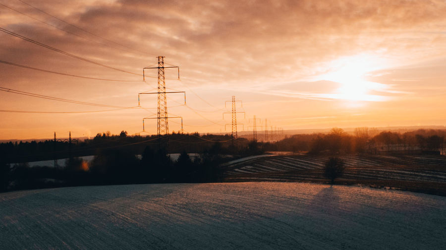 Electricity pylon on field against sky at sunset