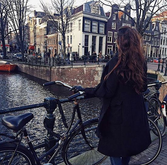 Woman standing by bicycle in city
