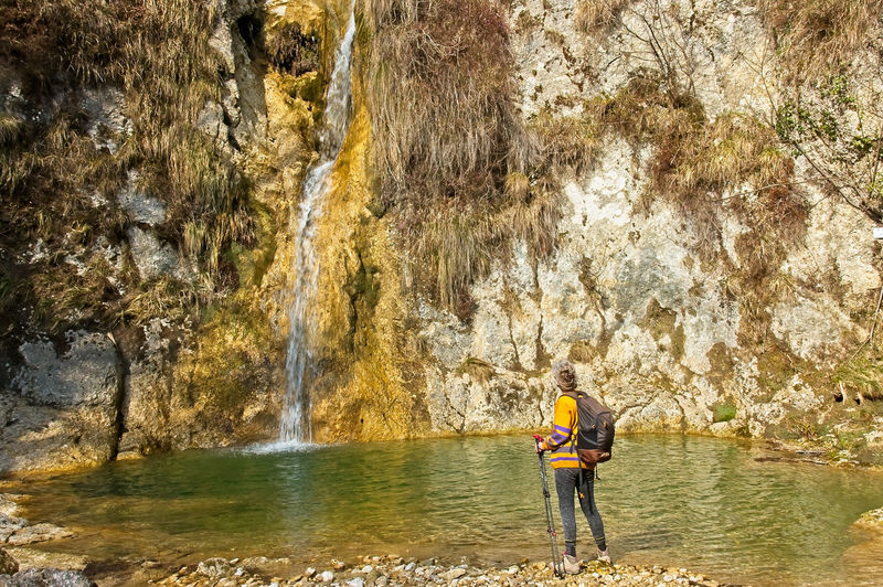 Man standing on rock by river in forest