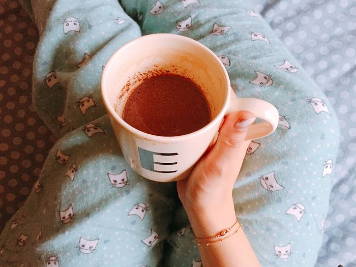 Midsection Of Woman Holding Hot Chocolate In Mug On Bed