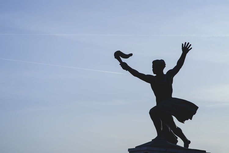 Silhouette of man with a torch in the complex of the Statue of Liberty in Gellert hill, Budapest, Hungary Arms Raised Art And Craft Cloud - Sky Creativity Day Human Arm Human Representation Limb Low Angle View Male Likeness Nature One Person Representation Sculpture Silhouette Sky Standing Statue Vapor Trail